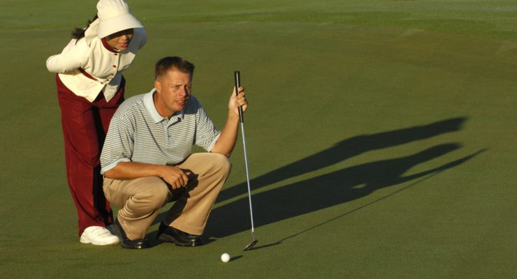 man playing golf with an assistant beside him