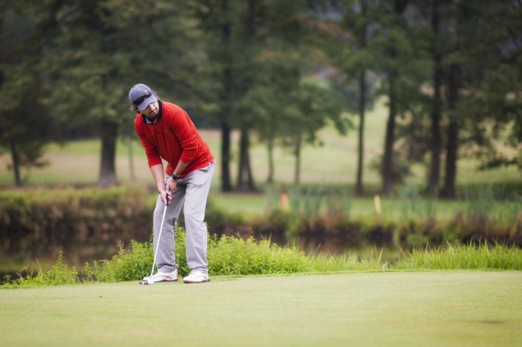 man in red sweater playing golf