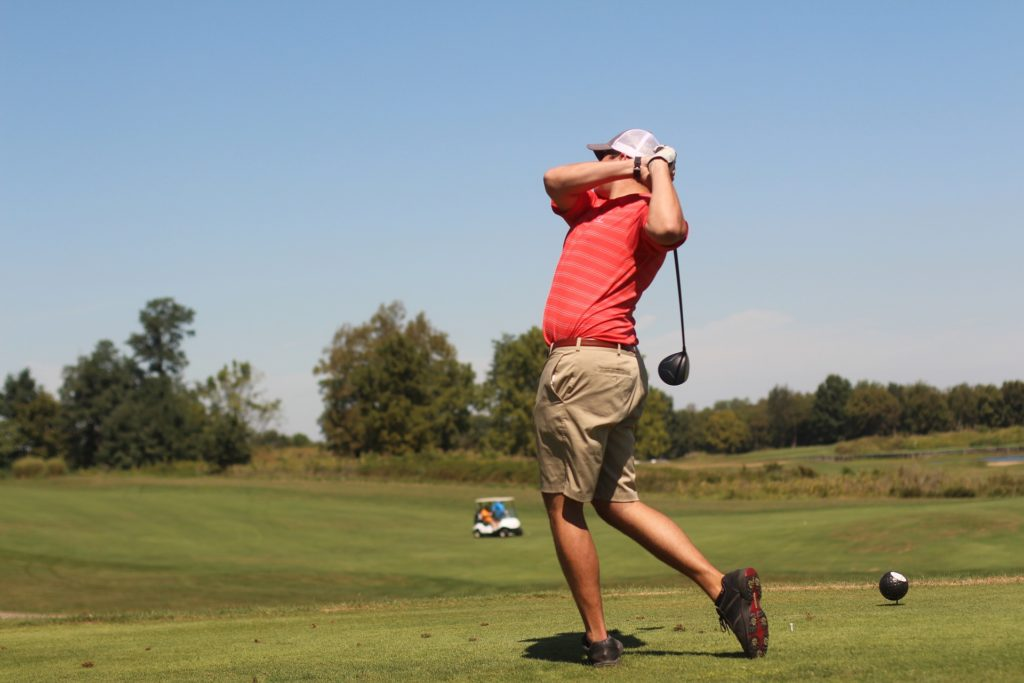 man in red shirt playing golf