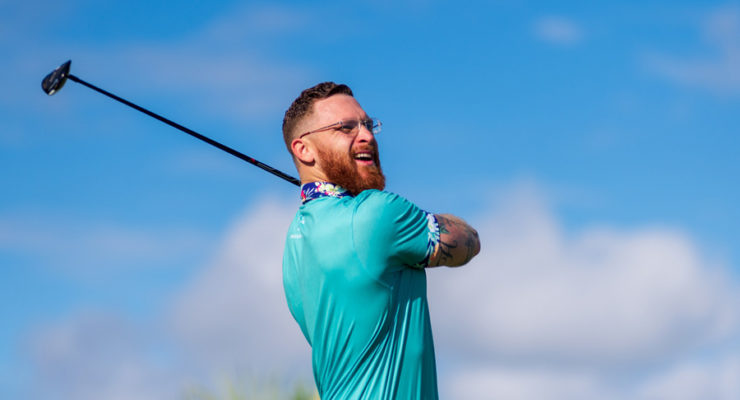 Golfer wearing blue shirts and playing golf