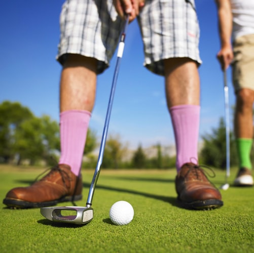 man wearing brown golf shoes with purple socks